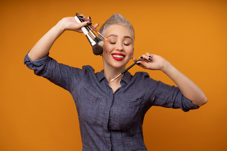 Close up portrait makeup artist. Make up courses. Concept of self visage masterclasses. Woman hold makeup brushes on the hands. Studio shot on the orange color background. Positive people smiling