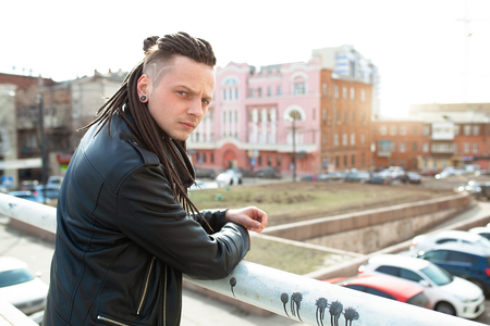 rocker rock star young caucasian man with dreadlocks walking on the city street autumn day. Dressed in the leather jacked 스톡 콘텐츠