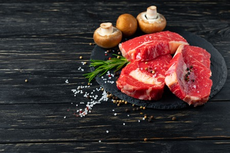 Three pieces of juicy raw beef with rosemary on a stone cutting board on a black wooden table background. Meat for barbecue or grill with Champignon mushrooms pepper and salt seasoning