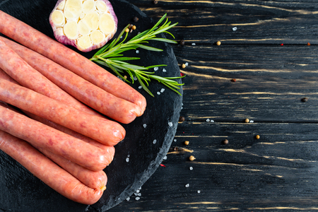 Juicy sausages for barbecue lie on a stone chopping board with rosemary garlic spices, pepper and coarse salt on the black wooden table background
