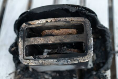 Burning toaster. Toaster with two slices of toast caught on fire over white background. Danger of careless handling of electrical appliances. Fire