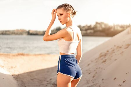 Beautiful athletic girl stands with her back near the lake after morning exercise. Back view of elastic female in beautiful shorts