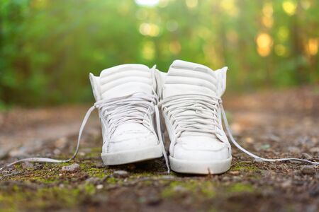 Used white high sneakers stand on a rural road that runs in the forest. Concept. Sport. Nobody comfortable shoes Stockfoto