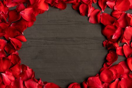 A round  frame made of rose petals on a dark cement table. Festive background is suitable for any holiday.