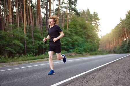 Athlète caucasien jeune homme blond bouclé exécute une journée d'été ensoleillée sur une route goudronnée dans la forêt de pins. Hommes 20 ans jogging dans la nature. entraînement pour le marathon. Concept de mode de vie sain. Banque d'images
