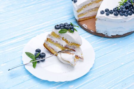 Appetizing cheesecake biscuit pillow decorated white cream blueberries and mint stands on wooden blue rustic table. Sweet cake with piece and spoon on plate Stok Fotoğraf