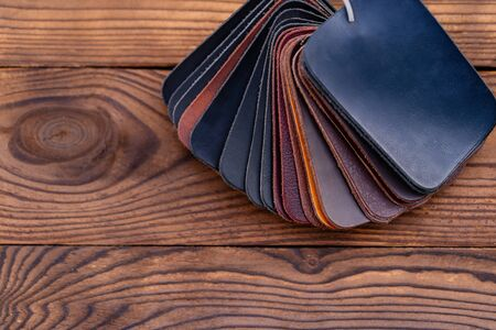 Leather samples for shoes on dark wooden table. Designer furniture clothes. Reklamní fotografie