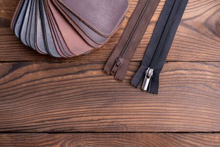 Leather samples for shoes and zipper  on dark wooden table. Designer furniture clothes. Stock Photo