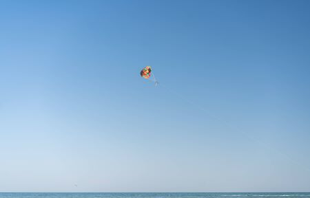 Fly with colorful parachute at the beach Parasailing people under parachute hanging mid air. Having fun. Summer Positive human emotions, feelings, family, travel, vacation.