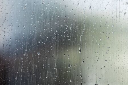 Gotas de agua sobre la superficie del vidrio de la ventana con fondo de naturaleza borroneada. Concepto de clima abstracto