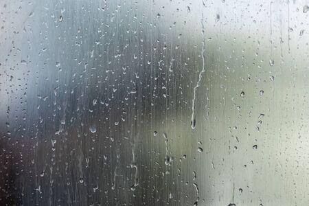 Wassertropfen auf Fensterglasoberfläche mit unscharfem Naturhintergrund. Abstraktes Wetterkonzept