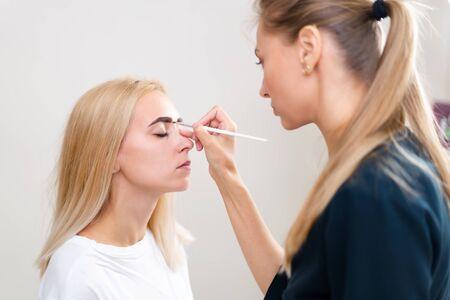 Kosmetikkabinett-Kunde sitzt auf der Couch. Kosmetikerin bringt Markierungen auf Augenbrauen an. Vorbereitung für das Verfahren des permanenten Augenbrauen-Make-ups. Freiraum. Schönheitsindustrie