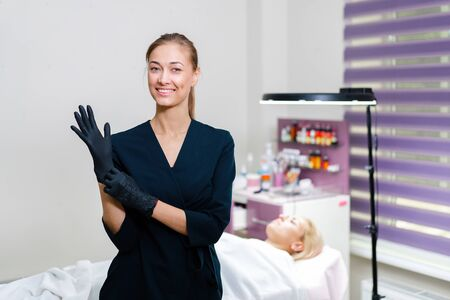 Cosmetology cabinet client lies on couch. Beautician stands puts black gloves on  hand and smiles. Preparation for the procedure of permanent eyebrow makeup.