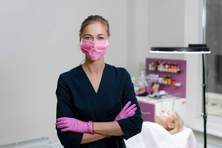 Cosmetology cabinet client lies on couch. Beautician stands in pink medical mask and smiles. Preparation for the procedure of permanent eyebrow makeup.
