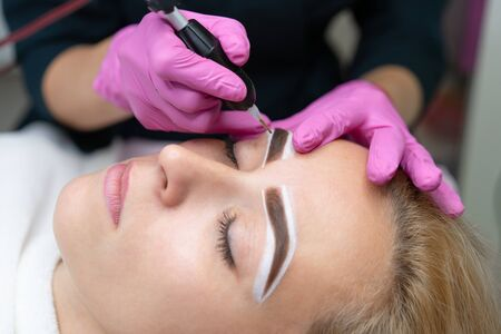Cosmetology cabinet client lies on couch. Beautician applies permanent ink on eyebrows. Procedure of permanent eyebrow makeup. Close up. Beauty industry Pink gloves