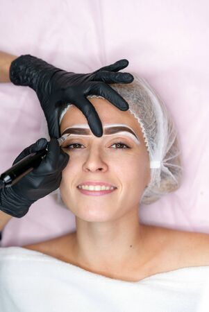 Cosmetology cabinet client lies on couch. Beautician applies permanent ink on eyebrows. Procedure of permanent eyebrow makeup. Close up black glove. Beauty industry