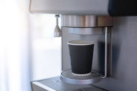 Coffee machine with paper cup and free space on the left For text. Professional machine for making coffee drinks.