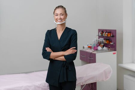 Cosmetology cabinet. Beautician stands in mask and smiles. Preparation for the procedure of permanent eyebrow or lips makeup. Cosmetologist in working space.