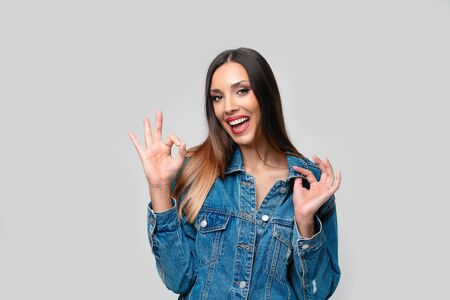 Beautiful caucasian girl denim jacket posing in studio on white background Cute brunette Denim fashion red lips makeup Young adult woman standing indoors surprised admired Shows ok sign gesture Imagens