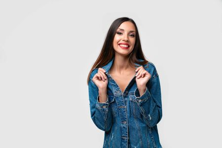 Beautiful caucasian girl denim jacket posing in studio on white background. Cute brunette. Denim fashion red lips elegant make up. Young adult woman standing indoors surprised admired