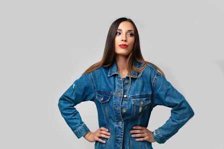 Beautiful caucasian girl denim jacket posing in studio on white background. Cute brunette. Denim fashion red lips elegant make up. Young adult woman standing indoors surprised admired Hand on hips