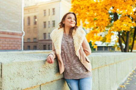 Beautiful caucasian brunette girl standing warm autumn day with background of trees with yellow foliage and a city. Dressed wool sweater and jacket. 版權商用圖片 - 132114218