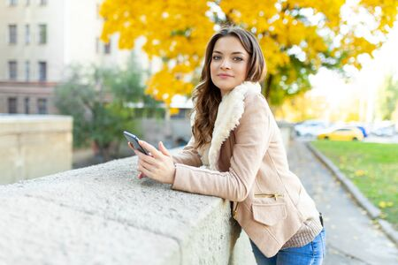 Beautiful caucasian brunette girl standing warm autumn day with background of trees with yellow foliage and a city. Dressed wool sweater and jacket. Holds mobile phone in hand looks at the screen.