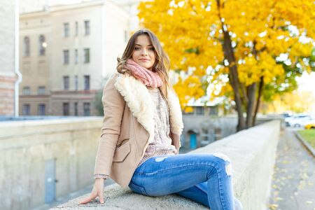 Beautiful caucasian brunette girl sitting warm autumn day with background of trees with yellow foliage and a city. Dressed wool sweater and jacket.