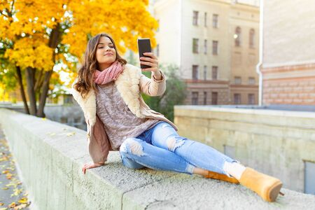 Beautiful caucasian brunette girl sitting warm autumn day with background of trees with yellow foliage and a city. Dressed wool sweater and jacket. Holds mobile phone in hand make selfie