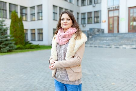 Beautiful European girl dressed warm autumn clothes walks  streets with office buildings  background. Dressed wool sweater and fashionable jacket. Lifestyle woman portrait. 版權商用圖片 - 132114517