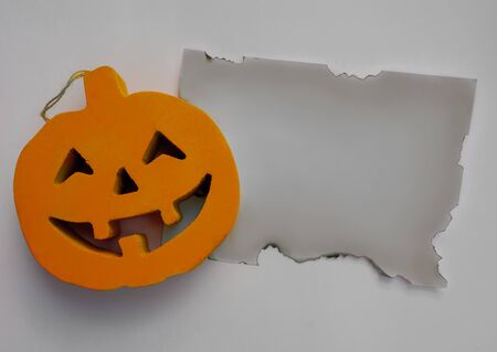 Halloween pumpkin with a burnt paper on a white background
