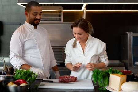 Handsome young African chef is cooking together with Caucasian girlfriend in the kitchen A cook teaches a girl how to cook. Man and woman cooking in professional kitchen. interracial relationship 写真素材
