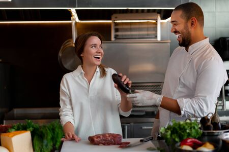 Handsome young African chef is cooking together with Caucasian girlfriend in the kitchen A cook teaches a girl how to cook. Man and woman cooking in professional kitchen. interracial relationship 版權商用圖片