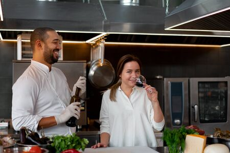 Handsome young African chef is cooking together with Caucasian girlfriend in the kitchen using red wine ingredient. A cook teaches a girl how to cook. Man and woman cooking in professional kitchen. 版權商用圖片
