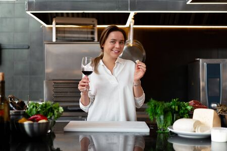 Beautiful young caucasian girl standing in kitchen in a white uniform smiling and tasting red wine Cute woman 30s years old in white shirt with food Ingredients cheese meat vegetables drinking 版權商用圖片