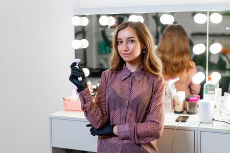 Beautiful young Caucasian makeup artist standing with tool in hands on background mirror in a beauty salon. Portrait of beautician at his workplace ready to work. 版權商用圖片