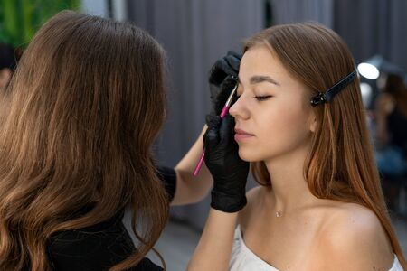 Young beautician caucasian girl holds model eyebrow correction Beautician at work is the workplace of an eyebrow specialist. Eyebrow correction and dyeing procedure. Beauty industry. Lifestyle
