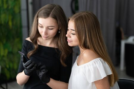 Young beautician caucasian girl holds model eyebrow correction Beautician at work is the workplace of an eyebrow specialist. Shutting result on phone Take a picture Beauty industry. Lifestyle
