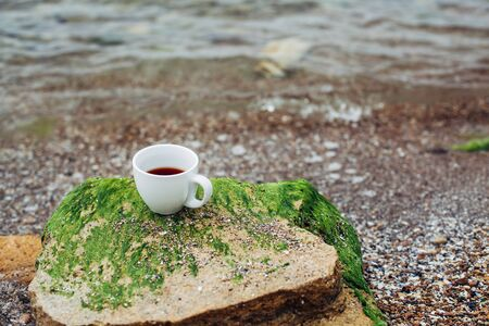 cup of coffee on the sea water and stone background. Sea freshness morning concept.