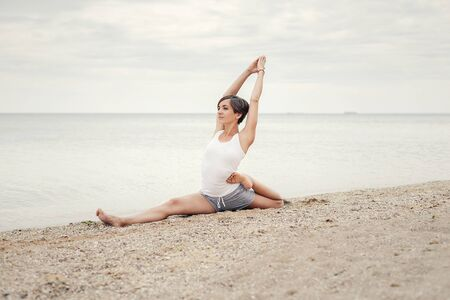 A girl with a short hairstyle dressed in shorts and a white jersey makes a twine on the background of the sea and the beach. Playing sports in nature. Stretching, Yoga pose.