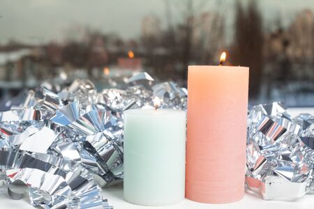 winter decor on windowsill with two candle and silver foil.