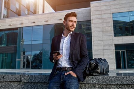 Young urban professional man using smart phone. Businessman holding mobile smartphone using app texting sms message wearing jacket With office buildings on the background 版權商用圖片