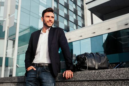 Mens fashion. A young male businessman in a trendy suit and a white shirt with a big black handbag comes out from a fashionable clothing store. Outdoor.