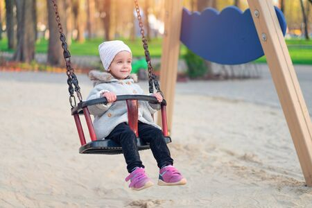 Happy child girl on swing in sunset fall. Little kid playing in the autumn on the nature park Adorable girl having fun on a swing on beautiful autumn day
