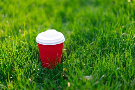 A red disposable cardboard cup with hot tea stands in fresh green grass. morning fresh concept 版權商用圖片