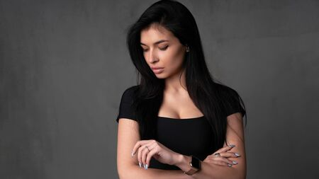 young caucasian brunette girl is standing in the studio on a dark background with something restless holds hands near her head Worried woman