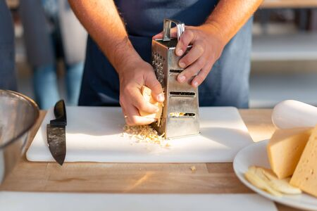 Close up of unrecognizable chefs hands grinding cheese on grater. On the side is a knife and a large piece of cheese. Cooking close up