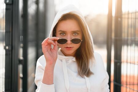 Outdoor close up portrait of young beautiful woman with long hair in sunglasses, dressed in a white hoodie sweater, near the sportsground. youth culture summer pastime