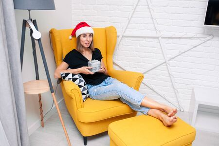 A young woman in a Christmas hat sits on a soft yellow chair at home, with a gift in her hands. Banque d'images