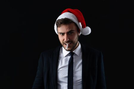 Young handsome caucasian guy in business suit and Santa hats stands on gray background in studio with serious face and smoking cigarette Portrait business person with Christmas mood Holiday banner Stock Photo